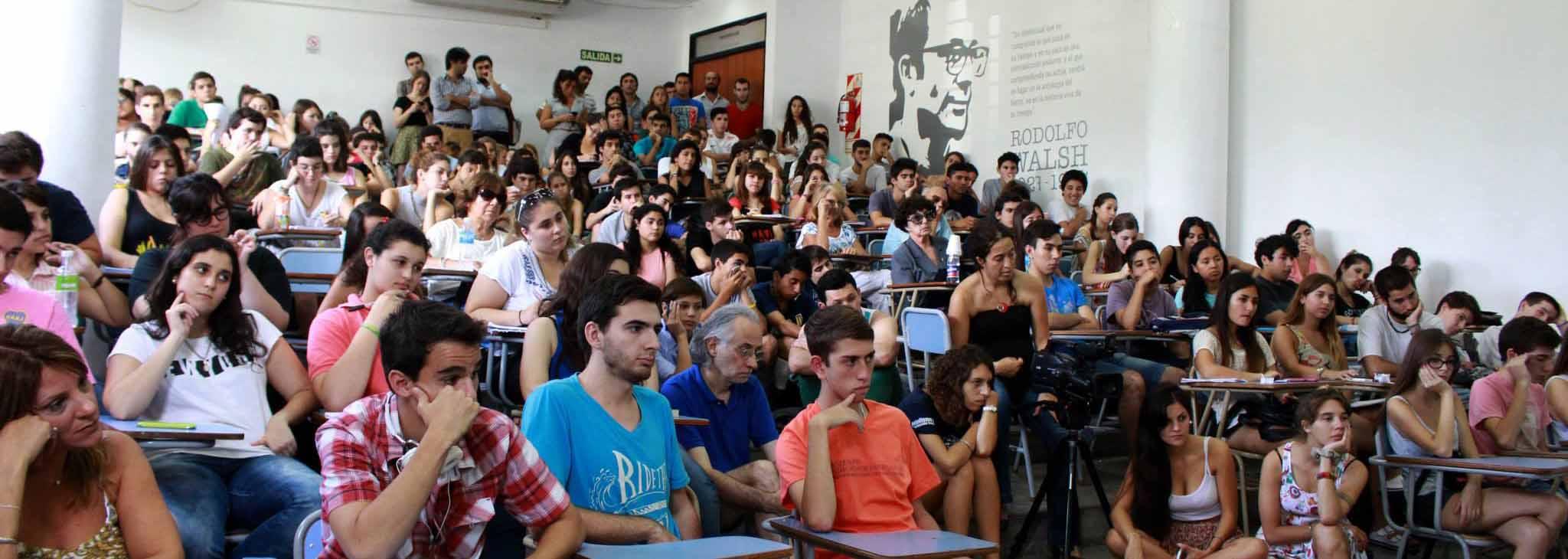 estudiantes de periodismo cursan en el aula anfiteatrada un teórico de la licenciatura