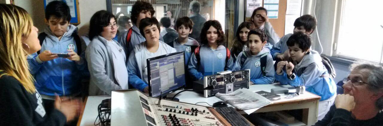 un grupo de chicas y chicos asisten a un taller de radio en el barrio