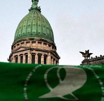 primer plano de un pañuelo verde con el congreso de la nacion de fondo