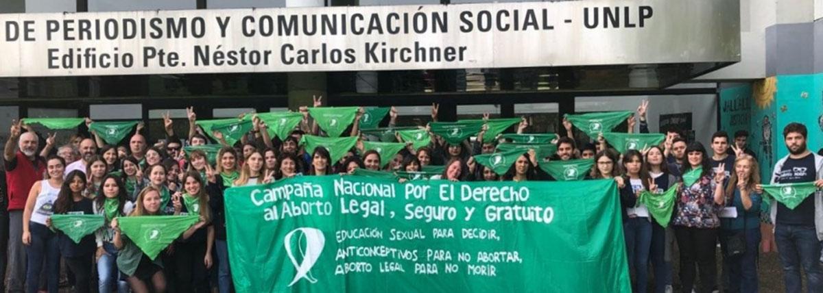 grupo de estudiantes y docentes de periodismo con pañuelos verdes y una bandera por el aborto legal