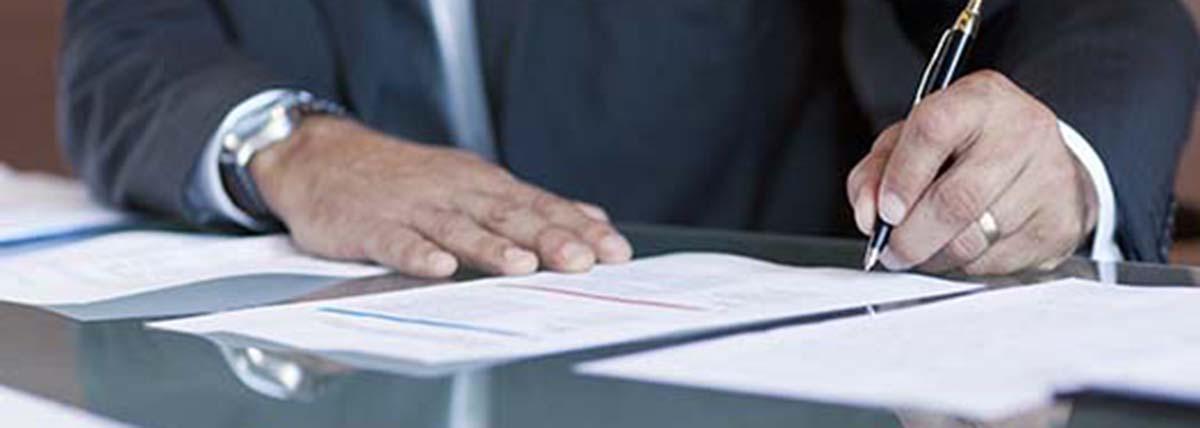 primer plano de una mano firmando un convenio