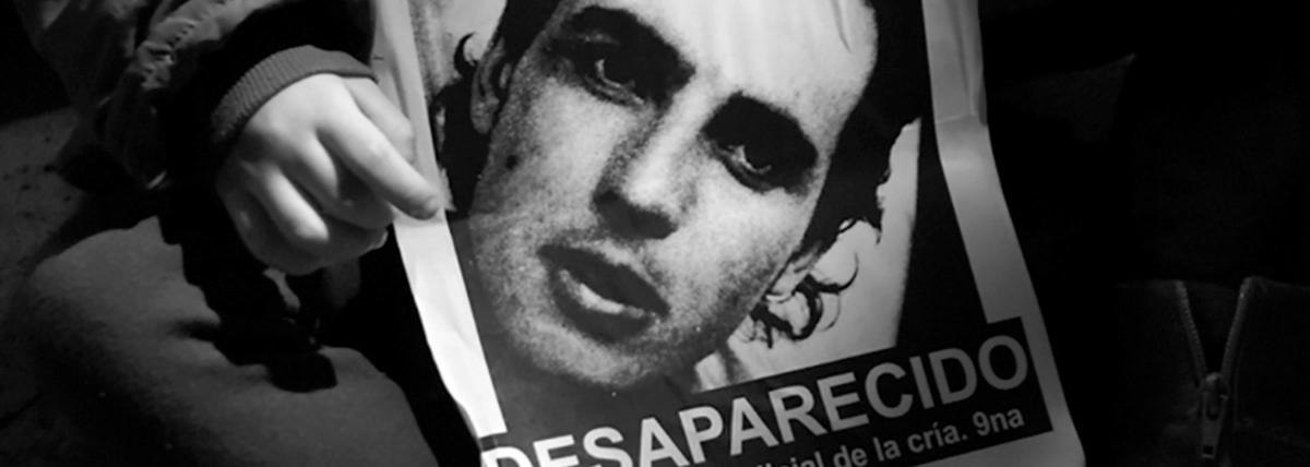 una mano sostiene un cartel con el rostro de miguel bru y la palabra desaparecido