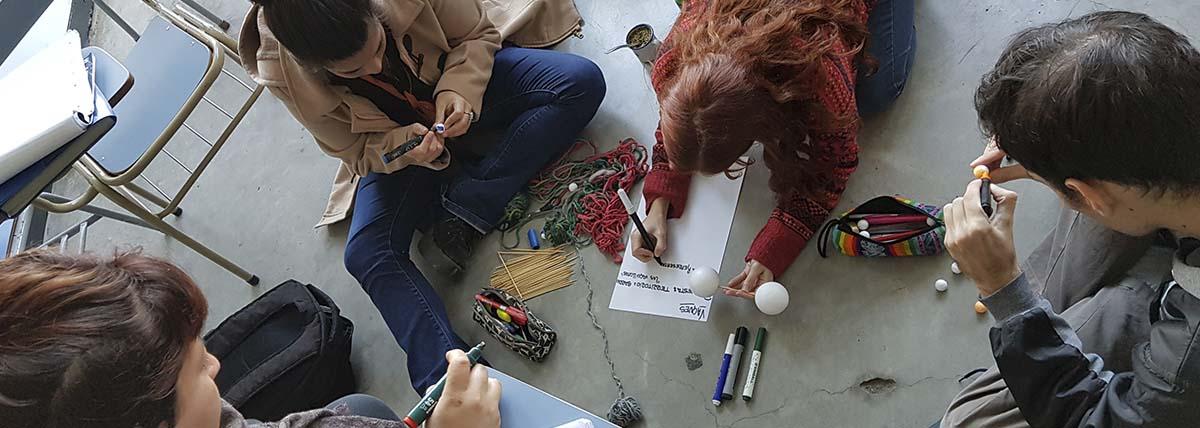 extensionistas confeccionan carteles para una actividad en el territorio