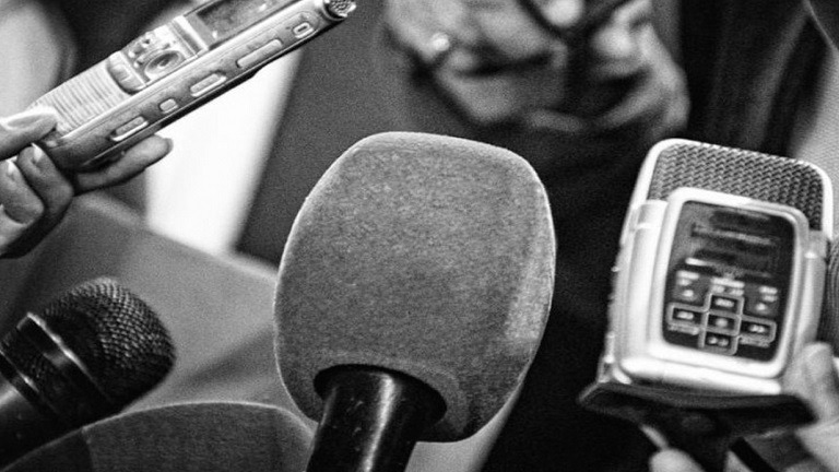 Foto de micrófonos en blanco y negro en alusión al Día del trabajador de Prensa