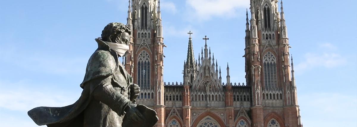 estatua en plaza moreno con barbijo y atras la catedral de la plata